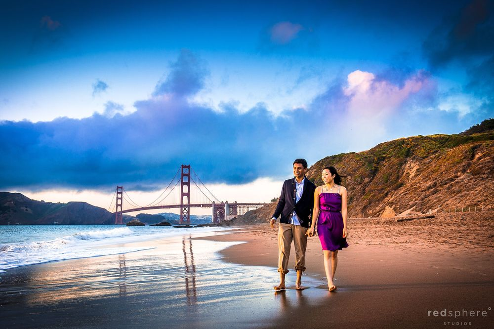 Couple Hand in Hand on Baker Beach, Golden Gate Bridge and Cotton Candy Skies