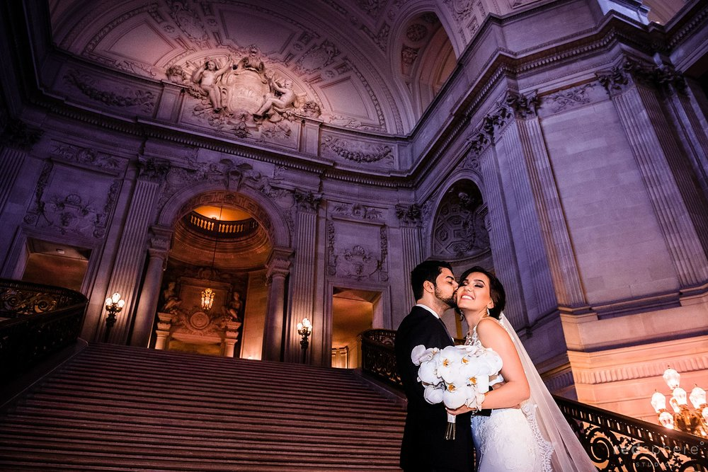 San Francisco City Hall wedding. Bride and groom standing on Grand Staircase