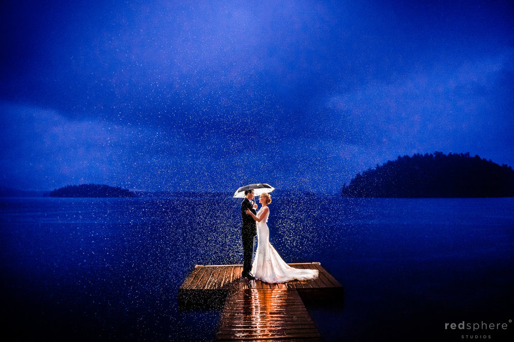 Bride and Groom Under an Umbrella on Saranac Lake Dock, Nightfall