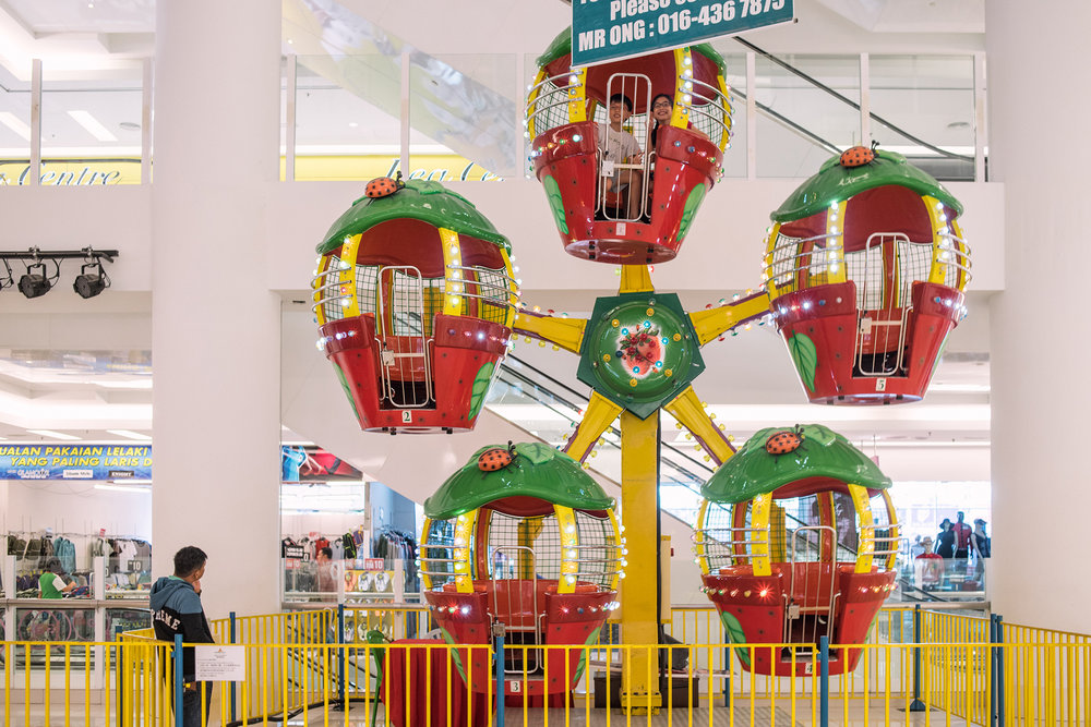 Their first time in an indoor ferris wheel. It cost about RM3.