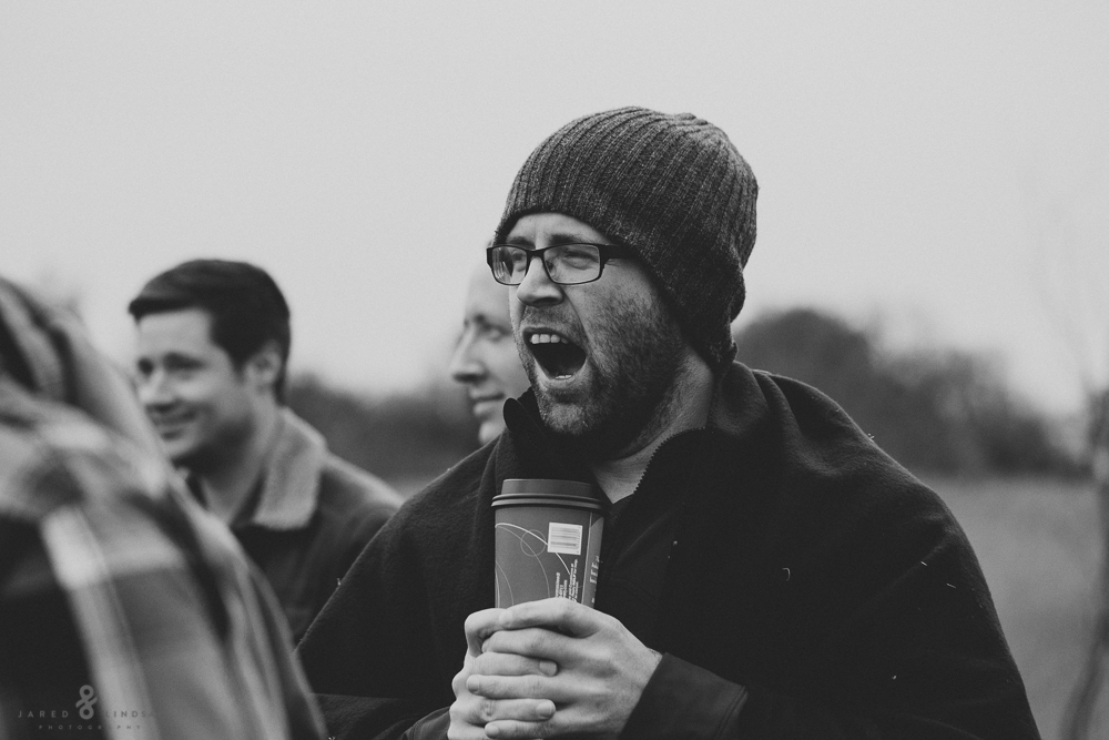 Man yawning while holding a cup of coffee