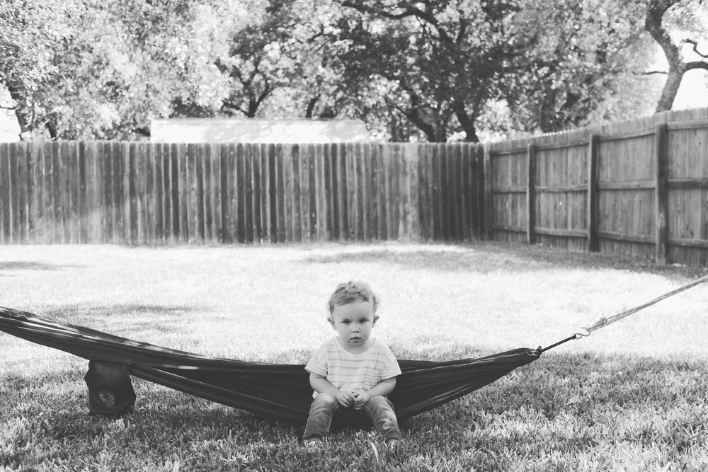 Child sitting in hammock in yard