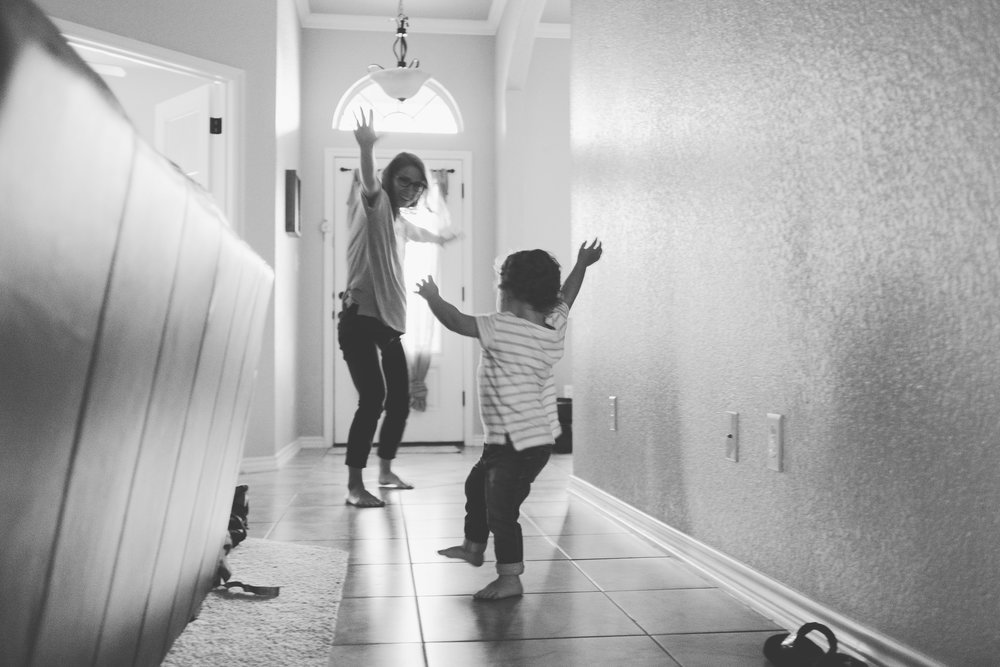 Woman and child dancing in hallway