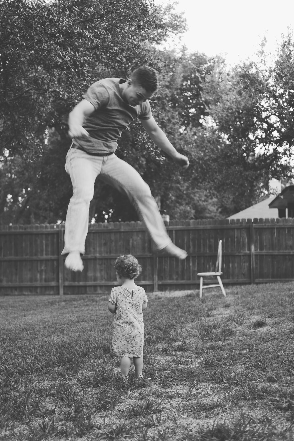 Man jumping over young child in yard