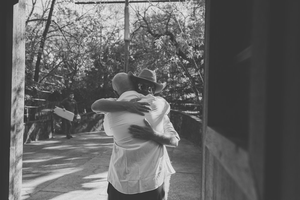 Groom hugging friend before ceremony