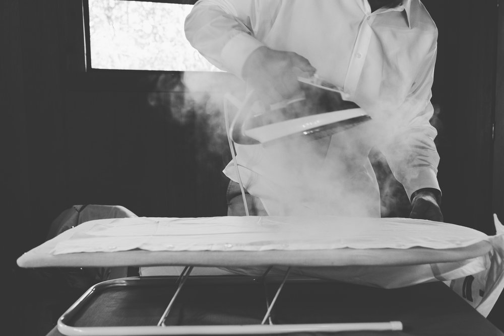 Man ironing a shirt with steam coming from iron