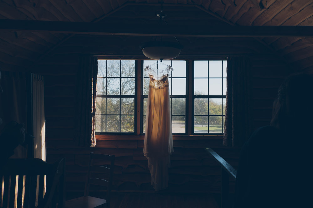 Wedding dress hanging in front of window