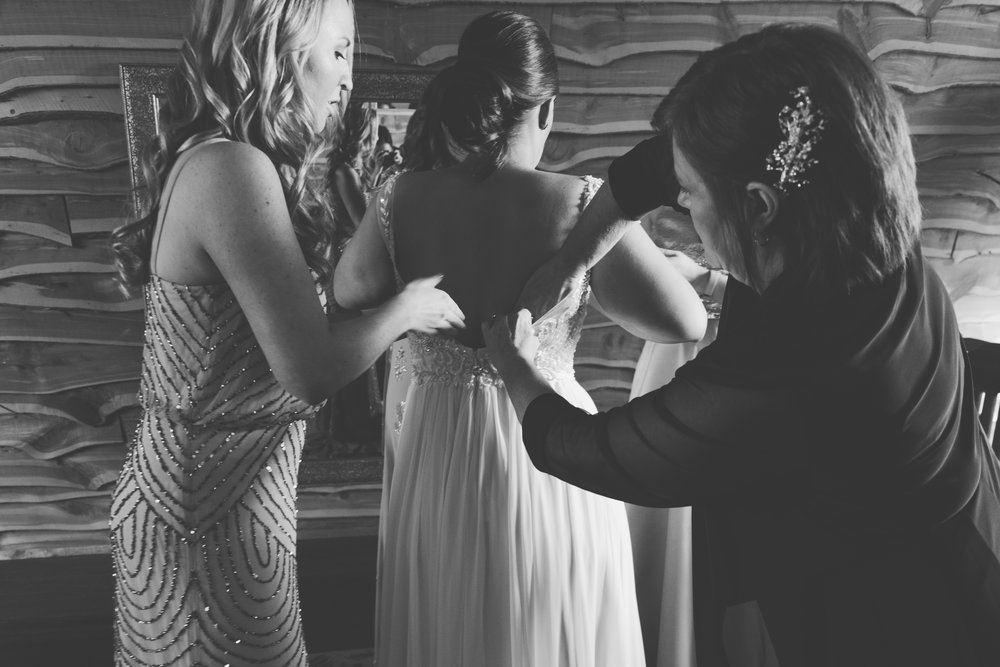 Mother of bride and brides maid helping bride put on wedding dress