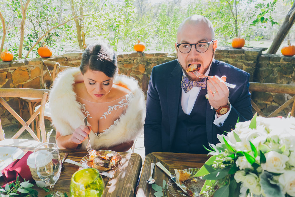 Photo of bride and groom eating at wedding reception