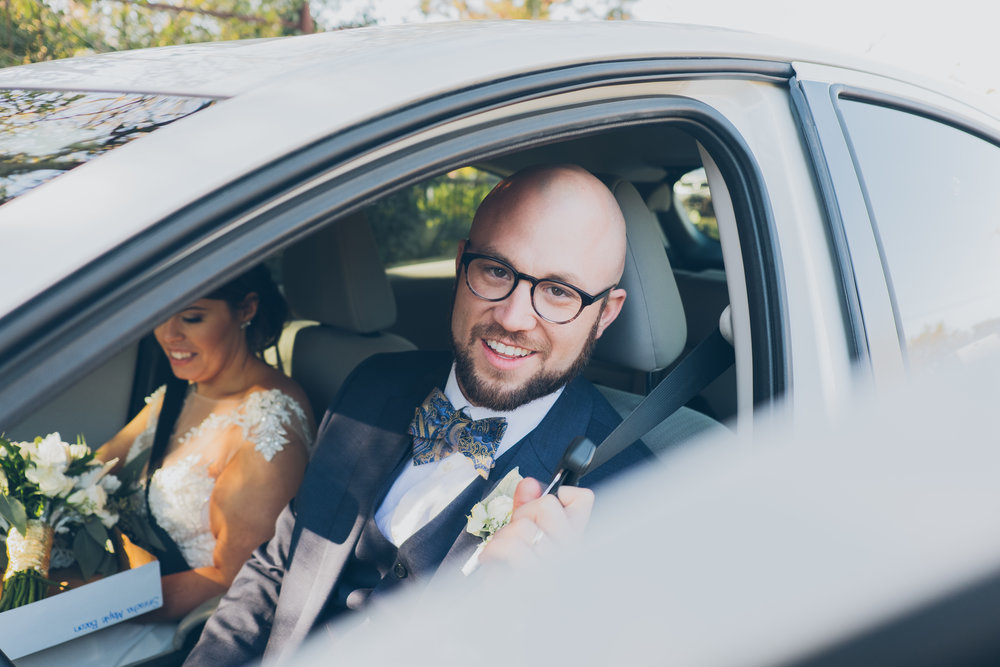 Bride and groom getting into car, leaving wedding
