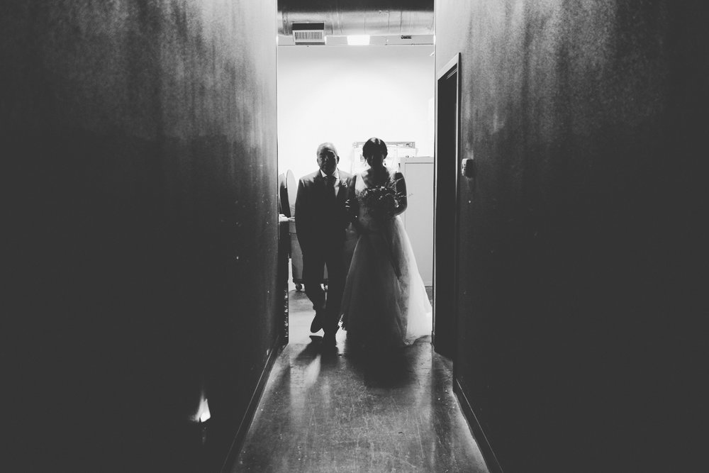 Father and bride walking down hallway.