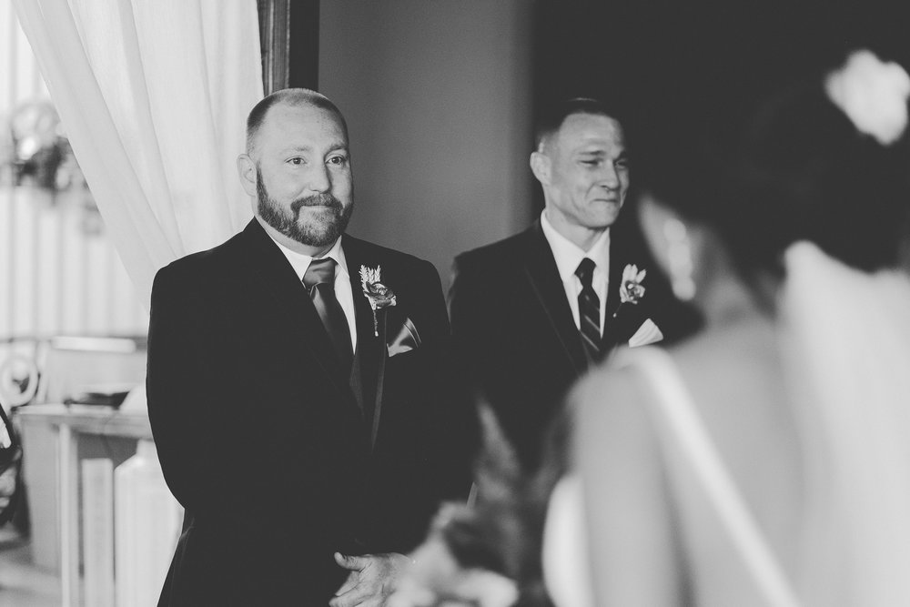 Black and white photo of Groom standig at the alter smiling as he looks at bride.