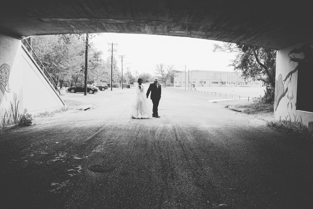 Black and white photo of bride and groom holding hands under a bridge