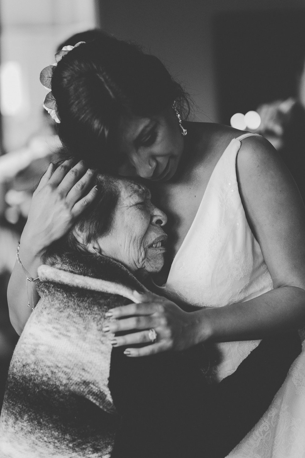 Wedding bride hugging old woman both crying.