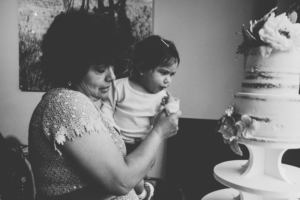 Black and white photo of a baby reaching for the wedding cake.