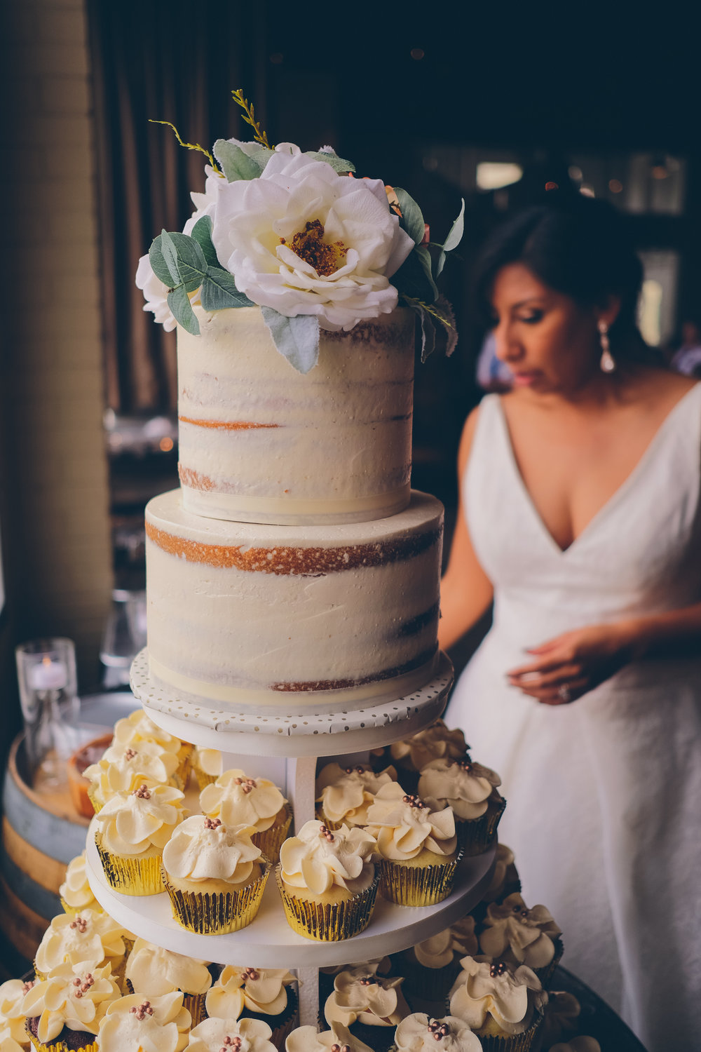Color photo  with wedding cake in foreground and bride out of focus in background.
