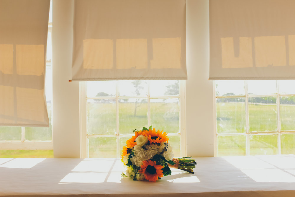 Bridal bouquet filled with sunflowers on empty table inferno of windows.