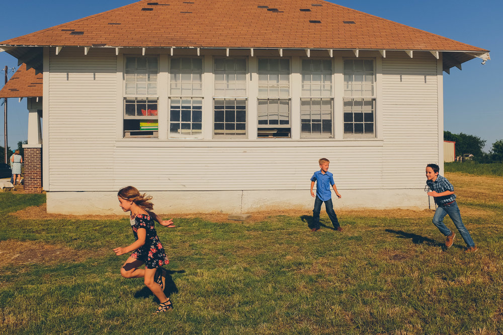 Children running around a building, playing tag.