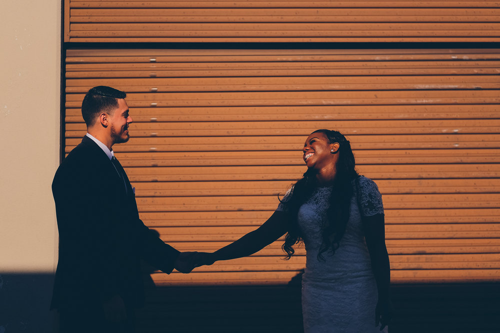 Color photo of bride and groom holding hands while laughing.