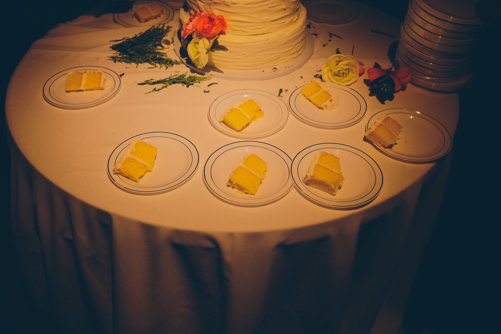 Color photo of table with plates of wedding cake sitting on top.