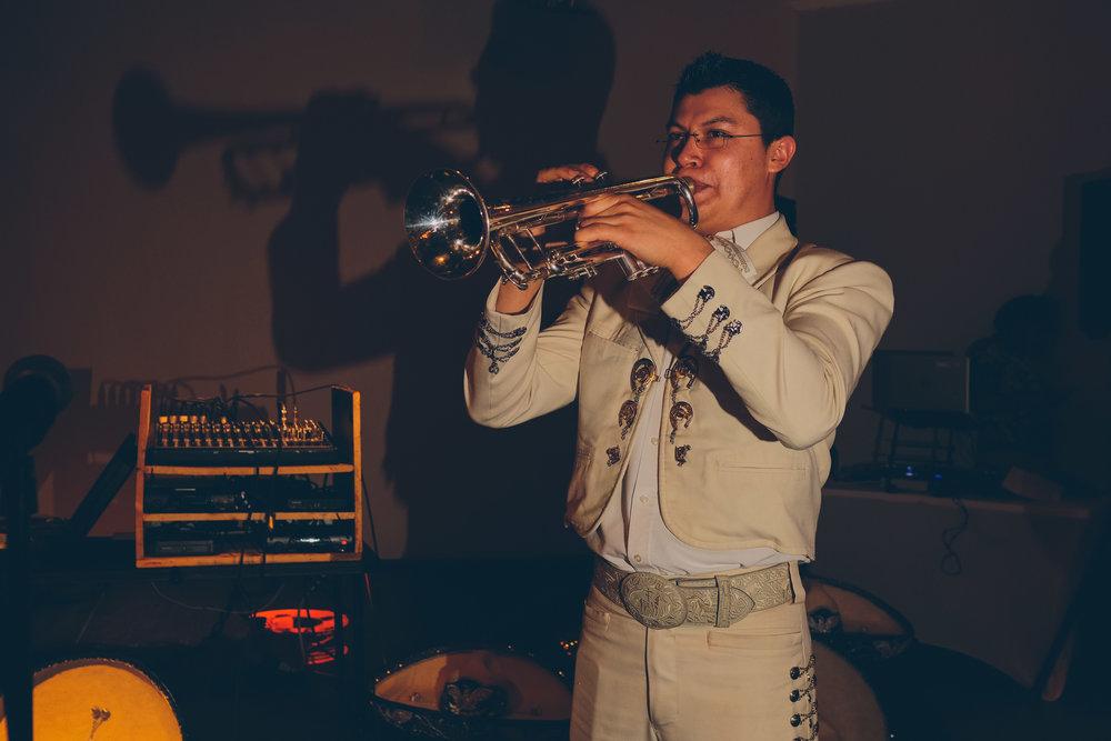 Man playing trumpet at wedding reception.
