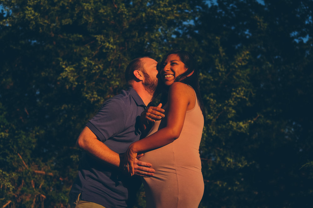 Couple kissing while holding woman pregnant belly