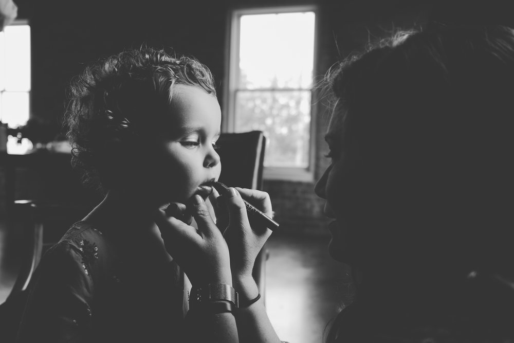 Black and white photo of a little girl putting on lipstick.