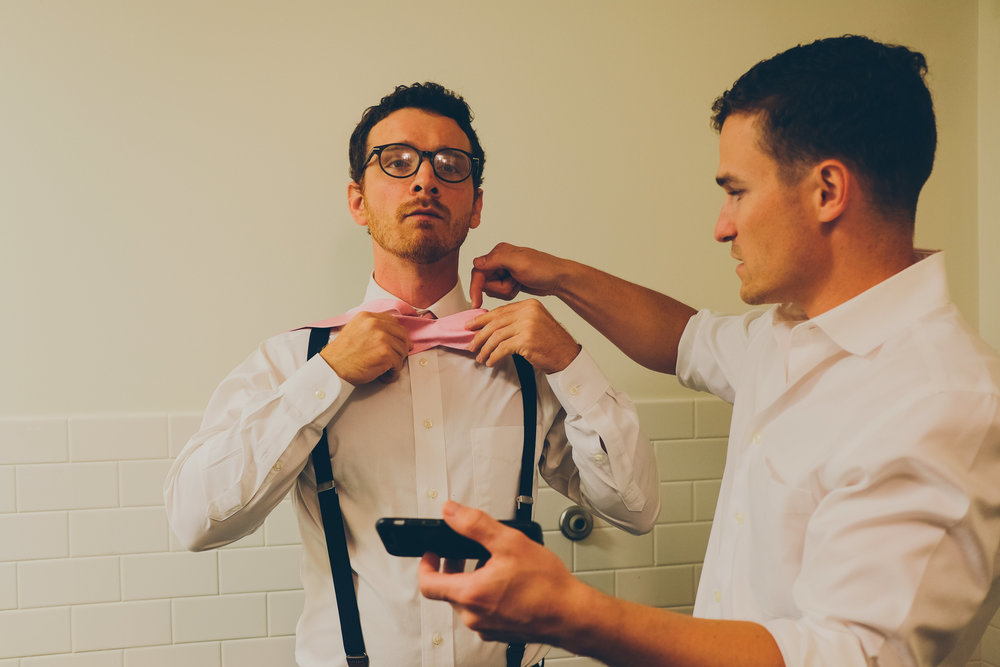 Photograph of a man helping a man tie a bowtie.