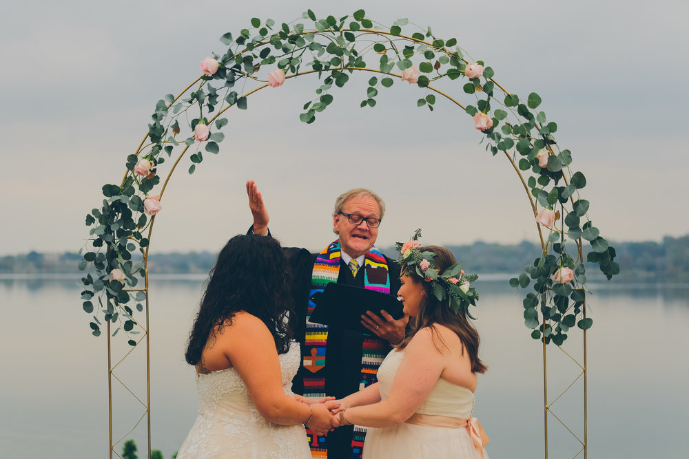 Photograph of two brides at same sex wedding ceremony.