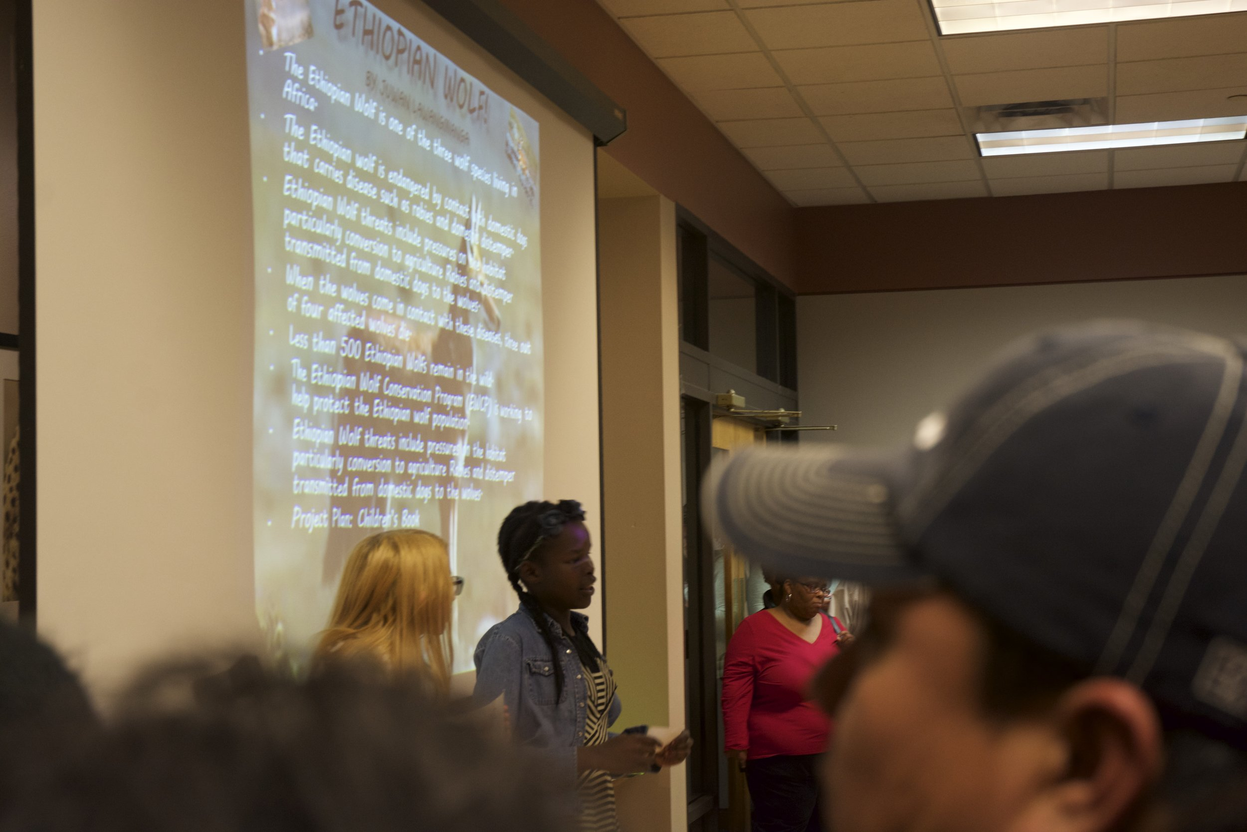 Caption: Juwan Lwangmianga, a seventh grade student at Croft Design Center Middle Prep, speaks to a packed room at the Nashville Zoo about Ethiopian wolves.