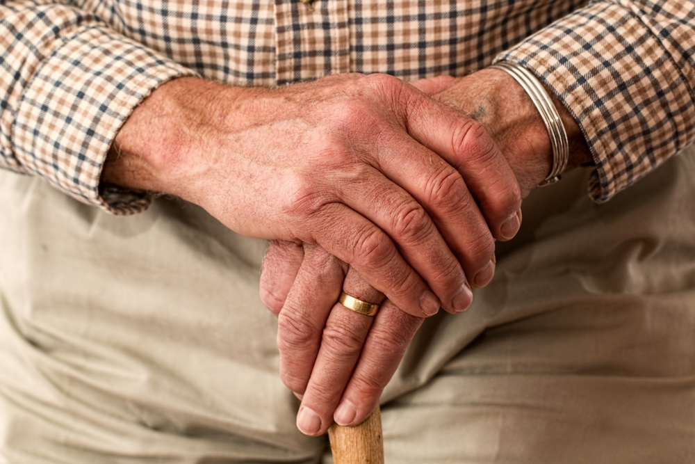 Hands of older man holding a cane