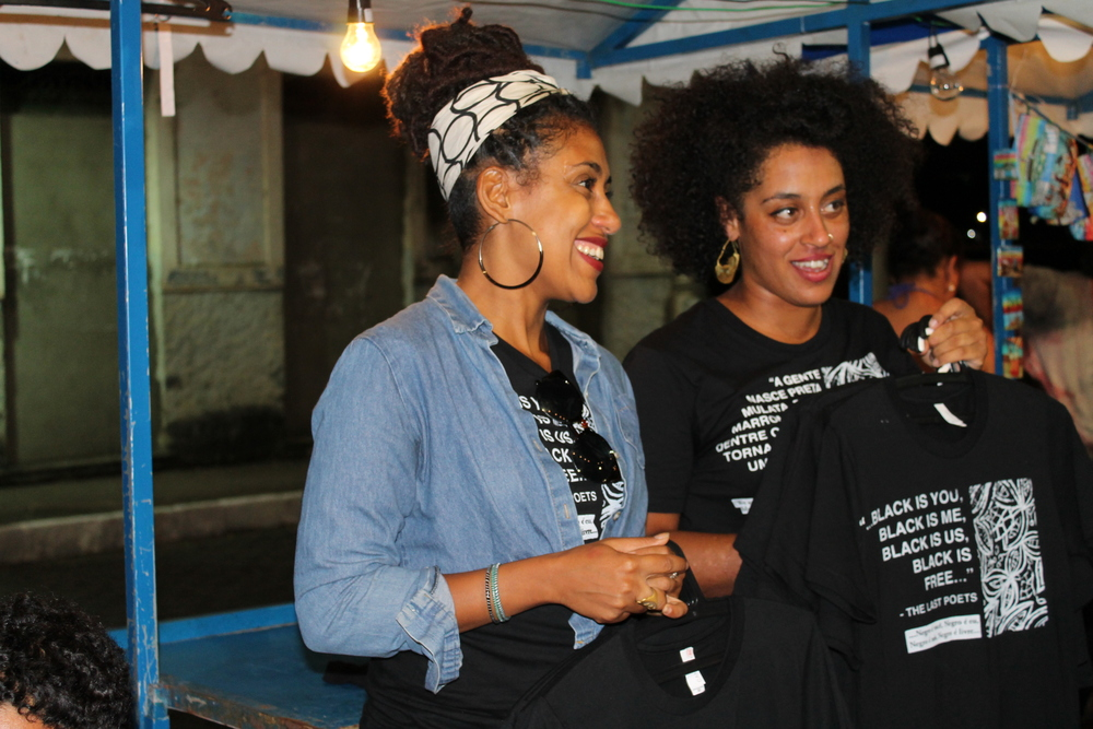 "Shani Peters and Sharita Towne, aka URe:AD Press giving free Afro-Brazilian and Black American pride message, hand-printed T-Shirts out to festival goers in Cachoeira, Brazil who were willing to come to the mic and answer the question: ""Why I Love Being Black?""."