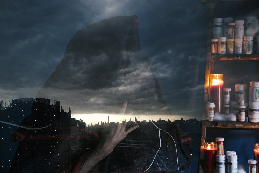 Long Black Veil - - -  [Image description: A large structure wrapped in black construction mesh stands against a cloudy skyline. Superimposed, a hooded figure draped in the same material stands beside a ladder packed with votive candles & one year's worth of prescription pill bottles.]