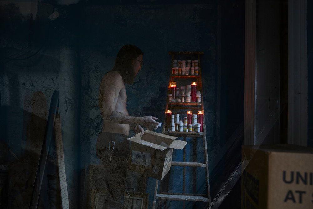 Daimones - - -  [Image description: Against the deep blue of a basement wall, a shirtless figure holds a cardboard box, making an altar of pill bottles and votive candles on an old wooden ladder.