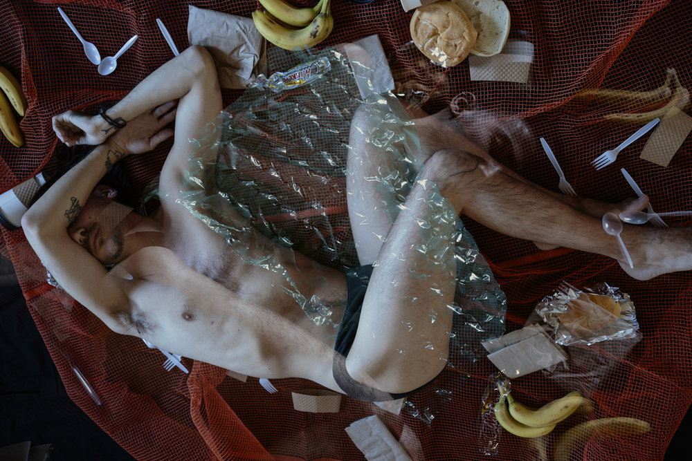 Horae (The Seasons) - - -  [Image description: A nearly-nude figure reclines on a sheet of orange construction mesh, surrounded by a week's worth of plastic utensils, coffee cups, napkins, bananas & deli rolls. Faintly overlayed, the same figure sleeps covered in bubble wrap.]