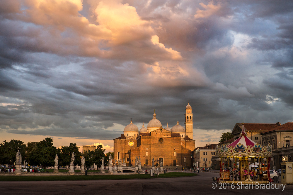 The Basilica of St. Giustina across the great piazza of Prato della Valle, and a merry-go-round (giostra) at dusk.