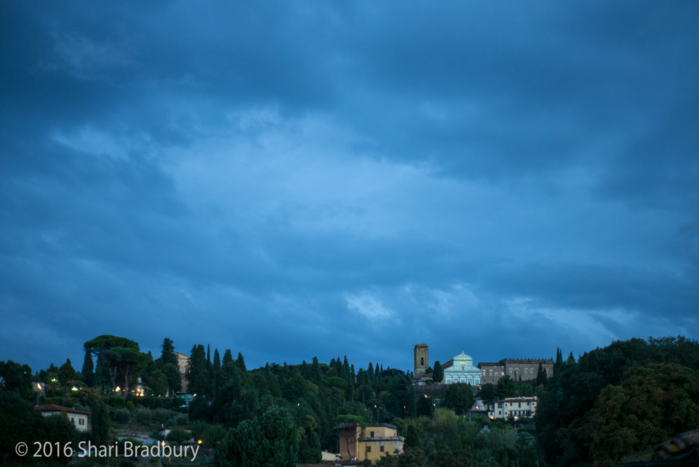 Looking out over the San Niccolo neighborhood toward Piazzale Michelangelo and Abbazia di San Miniato al Monte at dusk.