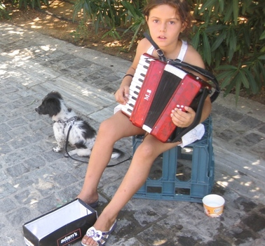 Young girl plays Accordion for tips on the street near the Acropolis in Athens.