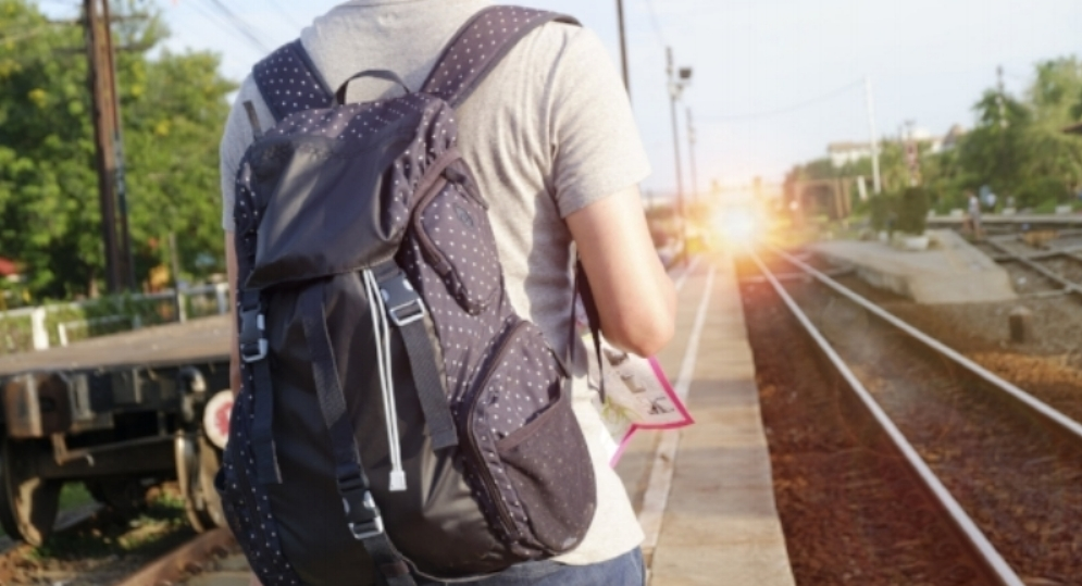 young man traveler with backpack  at the train station with a tr