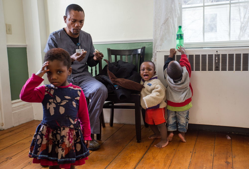 Jordan Shabani grabs a snack in the kitchen of his family's home before leaving for work, surrounded by his youngest children, Josephine Jordan (left), Msafiri (center), reacting to his father's impending departure, and Oredi, fascinated by Jordan's nearby soft drink. The Kalutas live in the Knox County town of Thomaston, population 2,781, because a nearby nursing home had jobs for the adults and was willing to arrange their housing and transportation to and from work. (Micky Bedell | BDN)