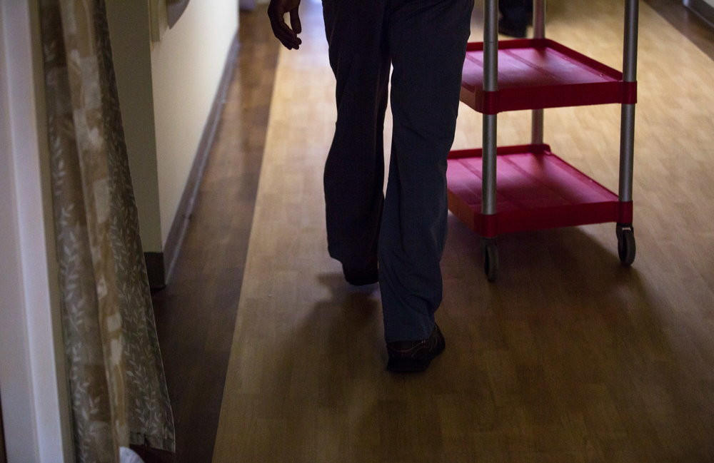 Jordan Shabani pushes an empty cart through the halls of the Crawford Commons nursing home in Union. Although thankful to have jobs and be living in America, the transition into Maine has been difficult for the Kaluta family. The family still has no independent mode of transportation, no way of easily visiting Congolese people elsewhere in Maine, and, apart from a few volunteers, no deepening ties to the community. While they are grateful to be in Maine, they often feel alone. (Micky Bedell | BDN)