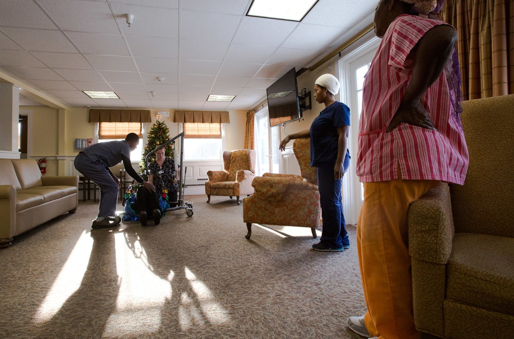 Mauwa Muyenga (far right) and Safi Paulo (second from right) watch as Jordan Shabani (far left) learns how to use a piece of nursing home safety equipment designed to help a fallen resident safely into a nearby chair from coworker Katherine Page and Resident Care Director Tara Sabins (being lifted) at the Crawford Commons nursing home in Union. A few months before the family learned they'd be going to the U.S., Chad Cloutier, the CEO and owner of a chain of 11 mostly rural Maine nursing homes called DLTC Healthcare, started casting a wider net to find employees. Like many long-term care facility owners across the state, Cloutier was struggling to find workers. (Micky Bedell | BDN)