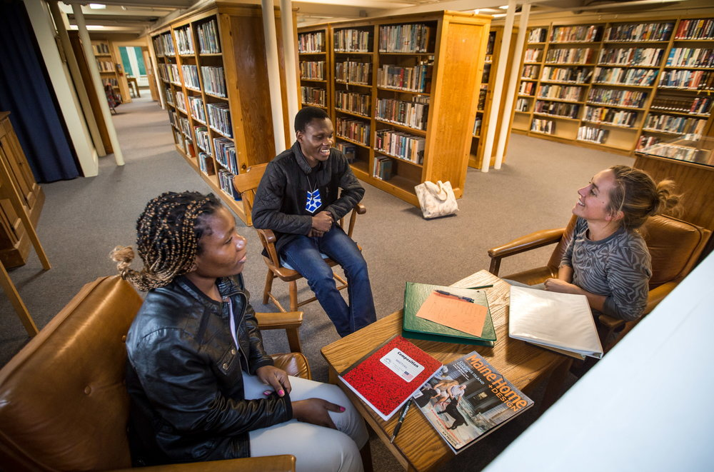 "Mzaliwa Kaluta (center) talks with English conversational partner Elizabeth Cuccinello (right) during a session with his sister Yalla Kaluta at the Thomaston Public Library. When Mzaliwa arrived with his family in the U.S. last July, he was ""too happy,"" he said, to finally be able to learn English and study at a good American school. Instead, he came to understand he must work. Yalla had already aged out of the school system by the time of their arrival. (Micky Bedell 