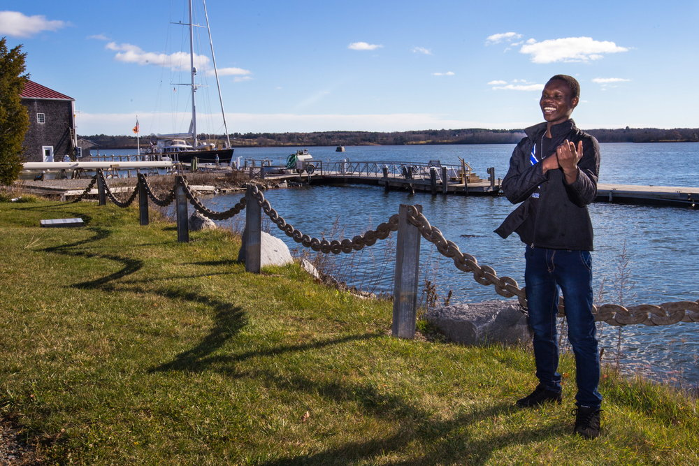 Mzaliwa Kaluta laughs while exploring Thomaston's public boat launch and landing area. He often walks around the town but is hesitant to go certain places because he isn't sure whether or not he's allowed to be there, and often struggles to understand any posted signs written in English. He was surprised and excited to discover he was allowed to sit by the ocean at the public landing. (Micky Bedell | BDN)