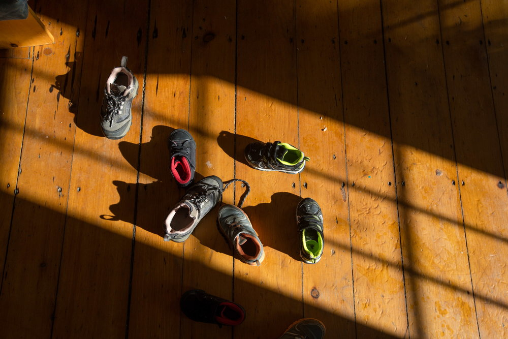 Multiple pairs of children's shoes litter the family's kitchen floor. There are nine family members under the age of 18 in the household, and three of them are under school age. With the recent exit of one of the adults to Portland, there are now only five working-age adults left to support the entire Kaluta family. (Micky Bedell | BDN)