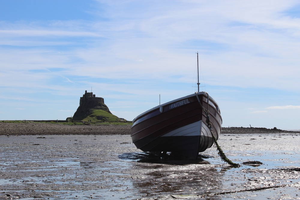 A Double ended work boat on the Holy Island of Lindisfarne. The 16th century Linidisfarne Castle can be seen in the background