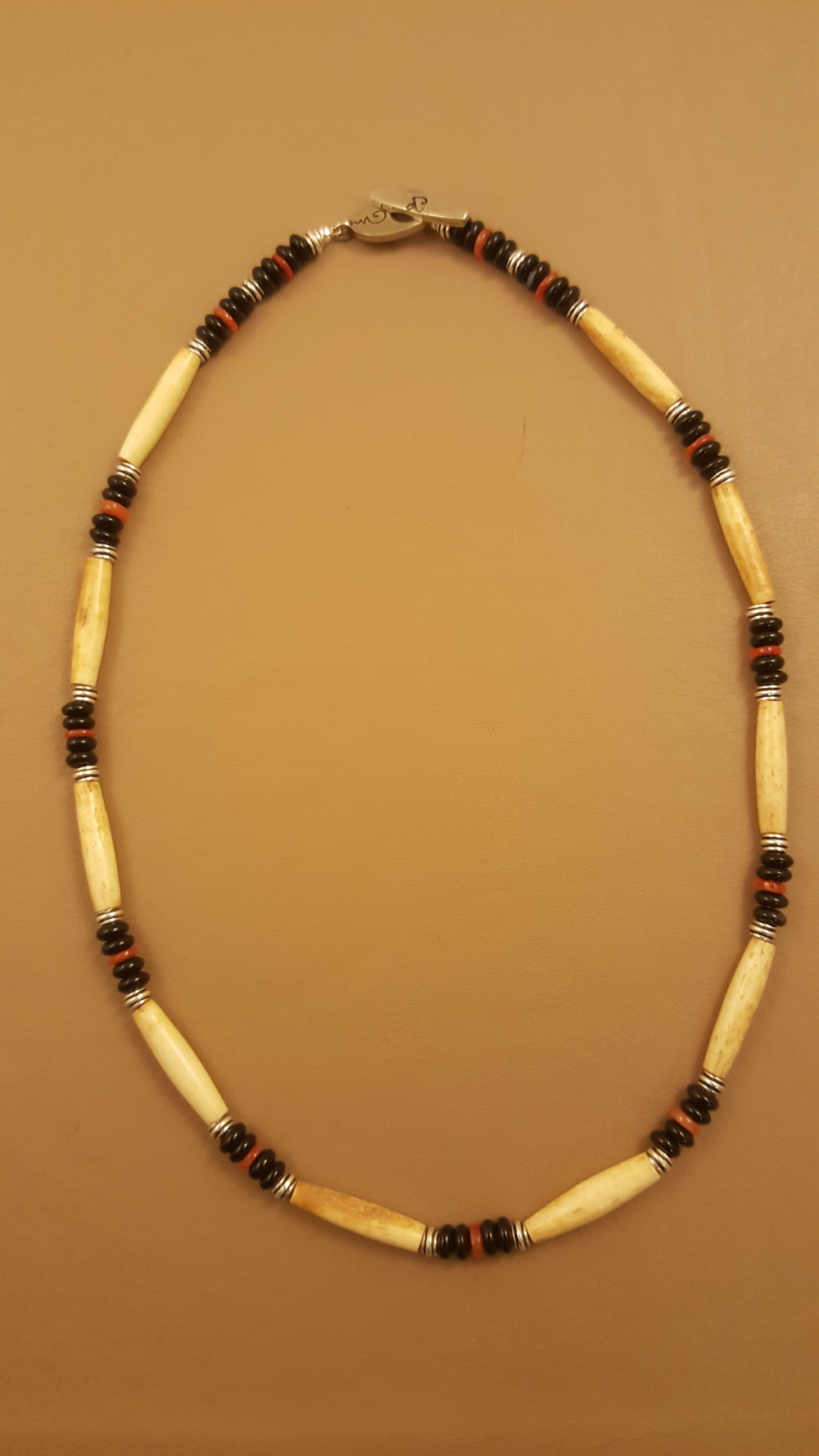 This single strand choker made with antiqued hairpipe bone beads, black onyx,carnelian, and sterling silver is easily a gender neutral piece of jewelry.