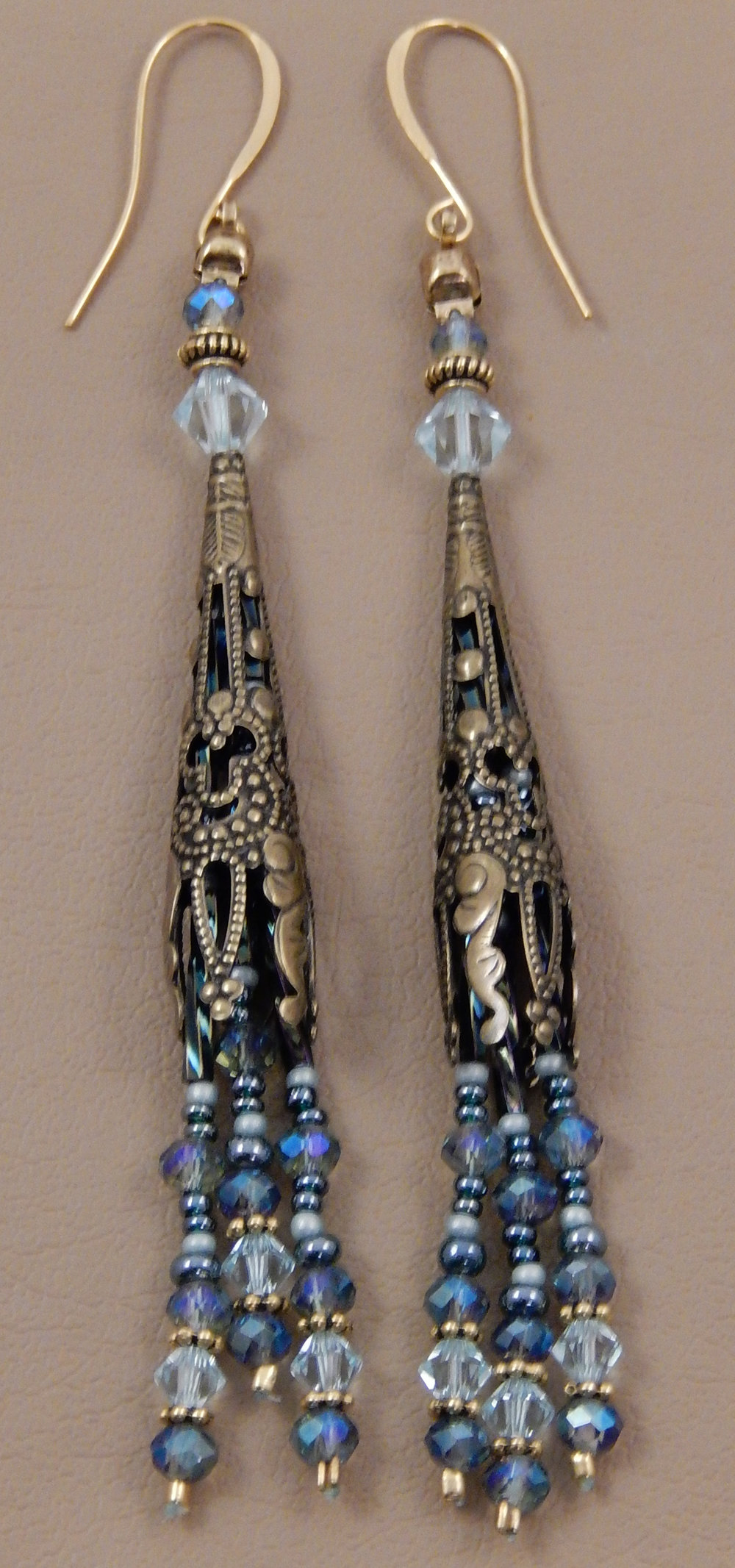 Decorative brass Bali style cone earrings featuring aquamarine swarovski crystals and light blue faceted round crystals.