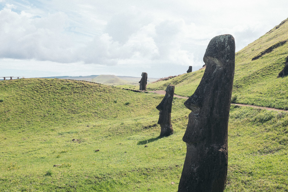 These frequently photographed Moai in the hillside are the statues still at the quarry where they were carved. For one reason or another they didn't make the journey across the island to their intended site and platform. There are dozens if not a hundred of them dotting the outer and inner side of the crater.