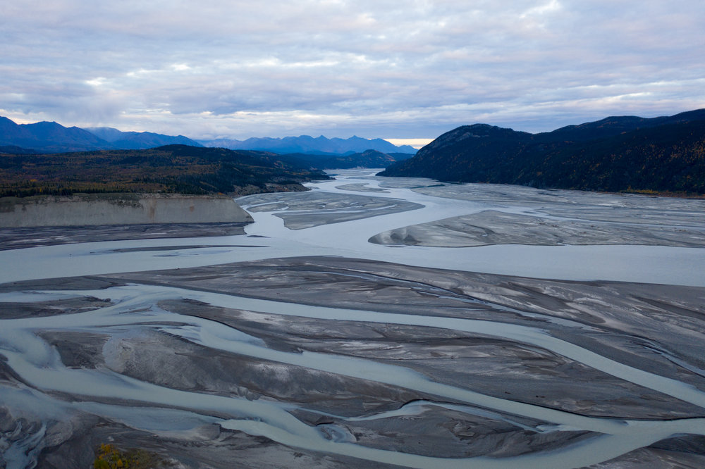 Drone shot looking down the milky glacier-fed Copper River into Wrangell-St. Elias National Park.